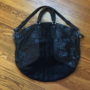 Leather and pony hair handbag with zipper details.